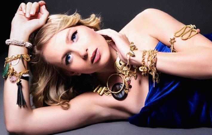 une femme allongée est couverte de bijoux en or