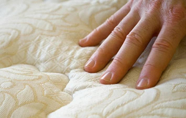 une main touche un matelas taché d'urine