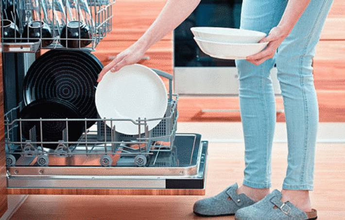une femme en pantalon turquoise sort des assiettes du lave vaisselle