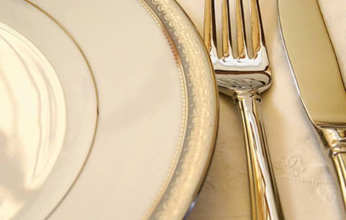 une assiette blanche bordé d'or avec à coté un couteau et une fourchette doré