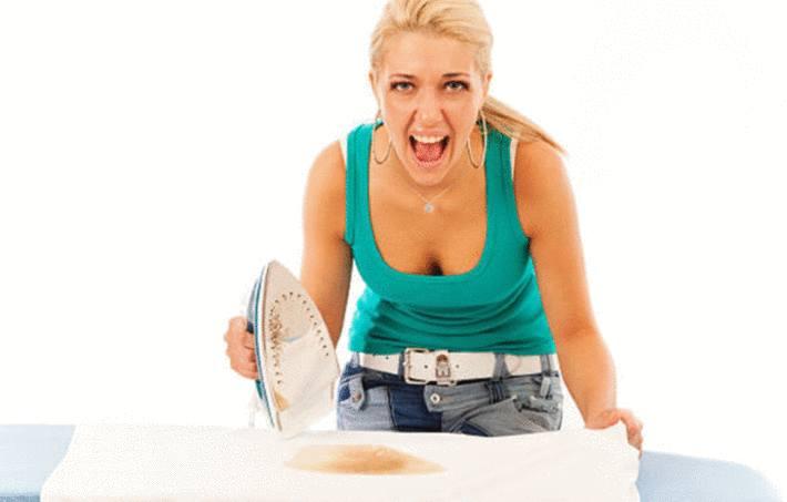 une femme qui repasse vient de faire une tache avec son fer à repasser