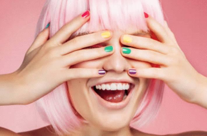 une femme cache ses yeux sous des mains avec des ongles de toutes les couleurs